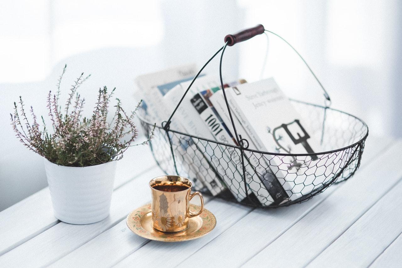 Potteplante og kurv med bøger står på hvidt bord