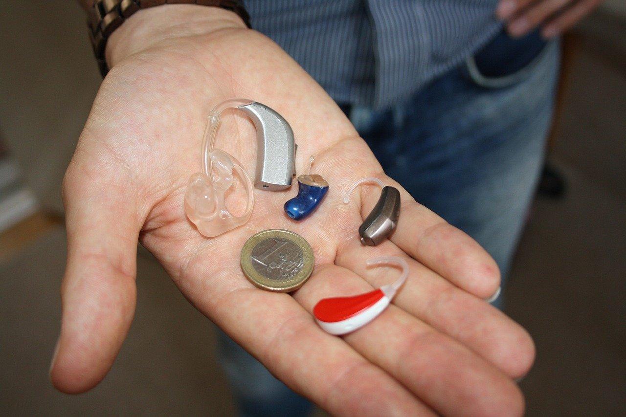 Person holder en forskellige høreapperater