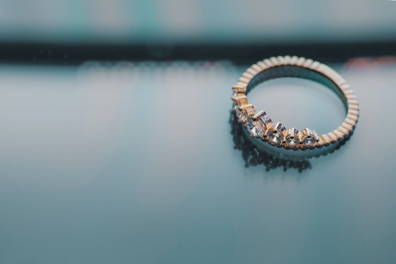 En enkelt guld ring ligger på glasbord
