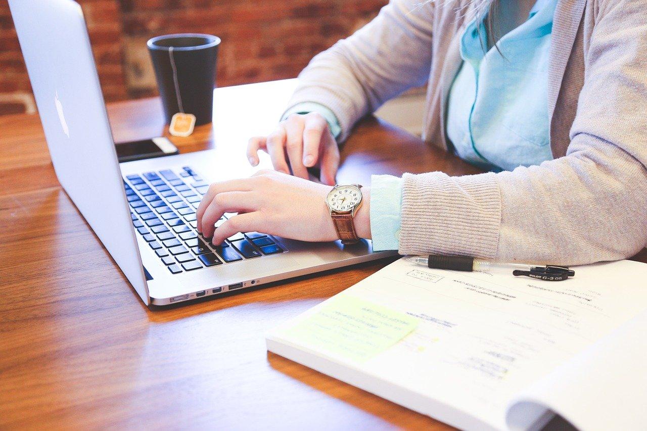 Kvinde arbejder på computer med notesblog ved siden