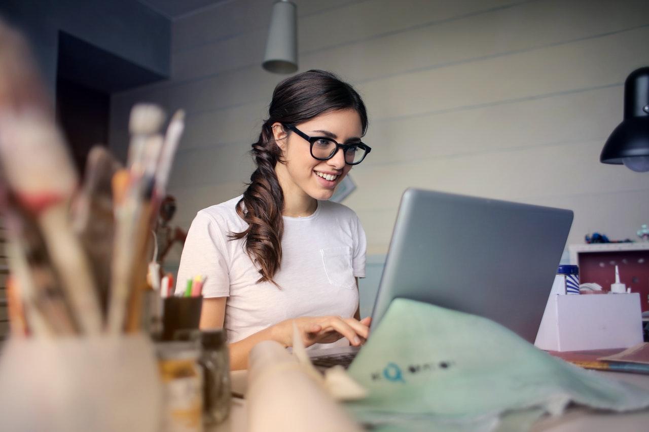 Kvinde er på computeren i godt humør