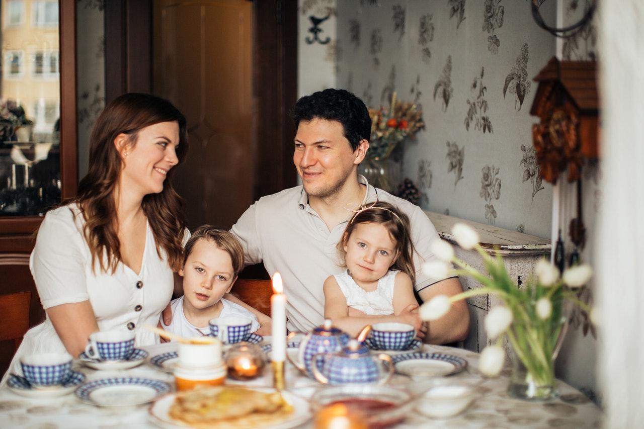 Familie sidder sammen og spiser morgenmad om sommeren