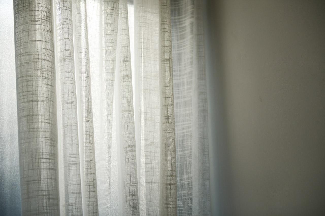 Hvide gardiner er rullet for på en solskinsdag