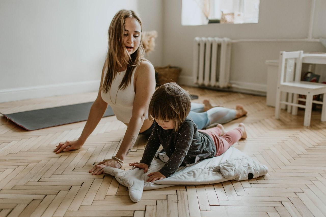 Kvinde og barn træner sammen i hjemmet