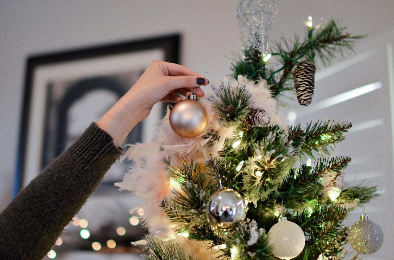 Person hænger pynt op på juletræ