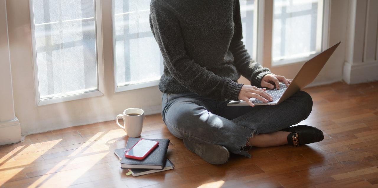 Person sidder på gulvet med sin bærbar computer
