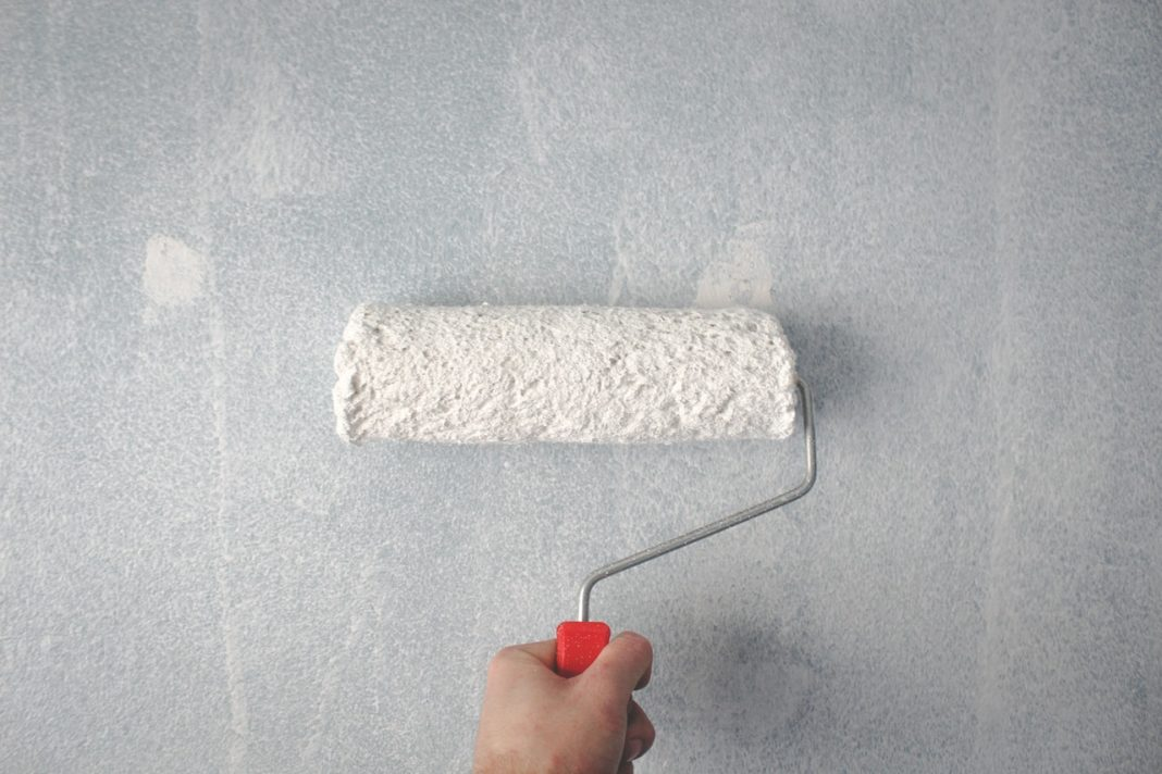 person maler væg med hvid maling